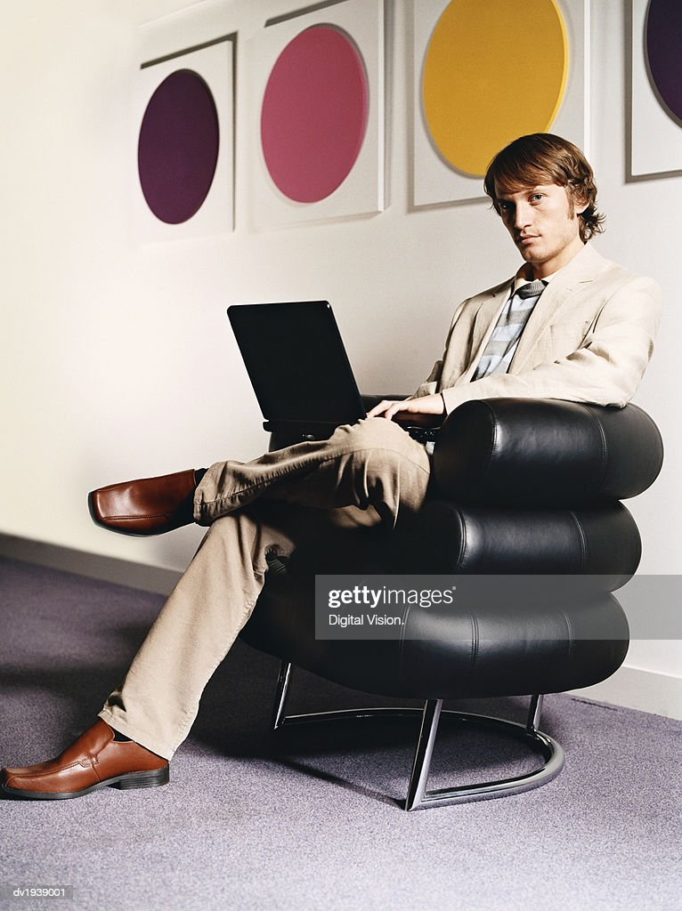 Young Businessman Sits in a Leather Armchair by a Wall, Using a Laptop : Stock Photo