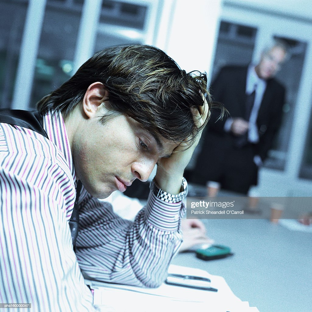Young businessman sitting at desk looking down, side view. : Stockfoto