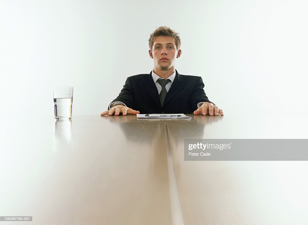 Young businessman sitting at end of table, portrait : Stock Photo