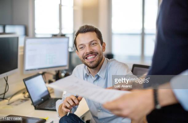 young businessman sitting at his desk and smiling - part of a series foto e immagini stock
