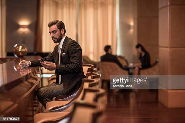 young businessman sitting at hotel bar reading smartphone texts - hotel stock pictures, royalty-free photos & images