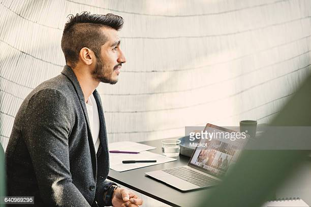 Young businessman sitting by table and looking away in creative office