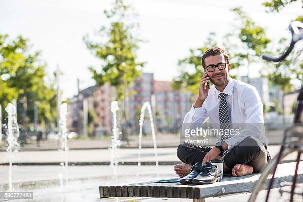 Young businessman sitting cross-legged on bench, using smartphone