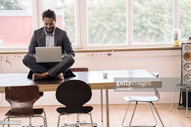 Young businessman sitting cross-legged on desk using laptop