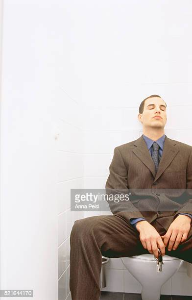 Young businessman sitting exhausted in the toilet