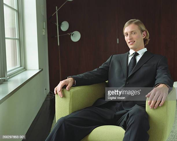 young businessman sitting in armchair, smiling, portrait - smug stock photos and pictures