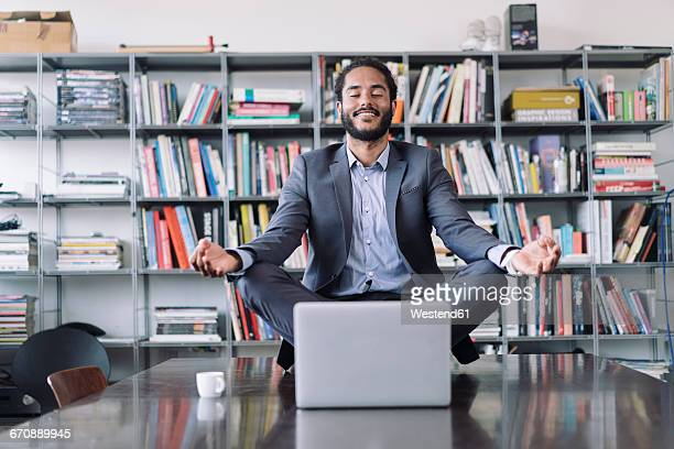 Young businessman sitting in office meditating in front of laptop