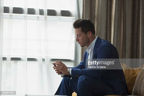 Young businessman sitting inside and text messaging, New York City, New York State, USA