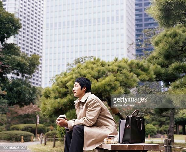 Young businessman sitting on bench in park, holding drink, side view