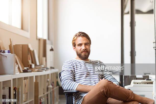 young businessman sitting on chair - lässige kleidung stock-fotos und bilder