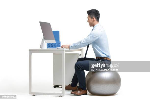 young businessman sitting on fitness ball while working in office - shirt and tie stock pictures, royalty-free photos & images