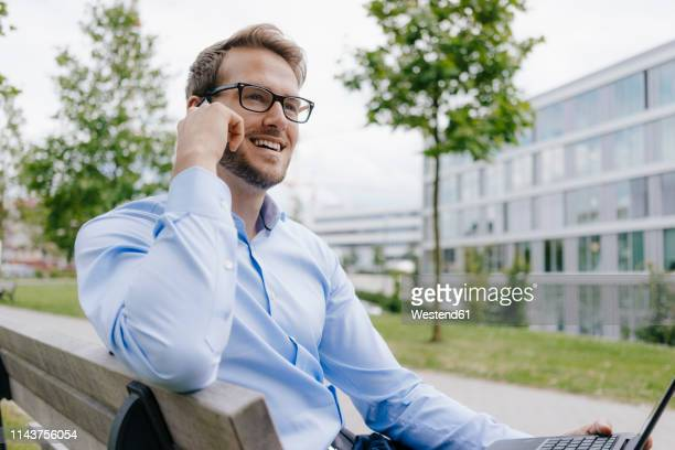 young businessman sitting on park bench, using smartphone - geschäftskleidung stock-fotos und bilder