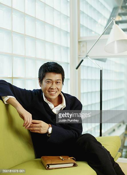 Young businessman sitting on sofa, smiling, portrait