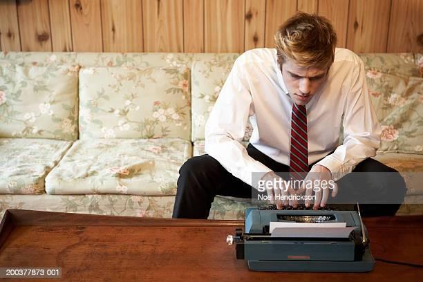 Young businessman sitting on sofa, using typewriter