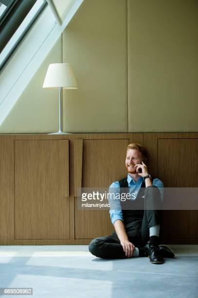 Jeune homme assis sur le sol et parler au téléphone