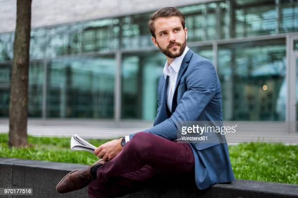 Young businessman sitting outdoors with newspaper
