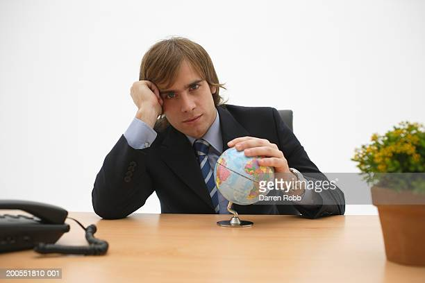 Young businessman sitting with hand on globe at office desk, head in hands, portrait