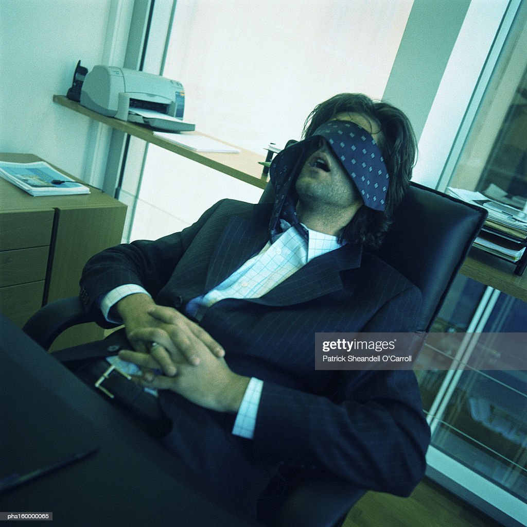 Young businessman sleeping at desk, tie covering eyes. : Stockfoto