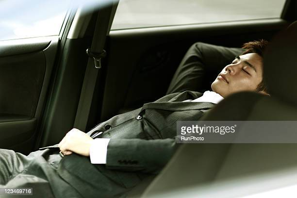 young businessman sleeping in the car