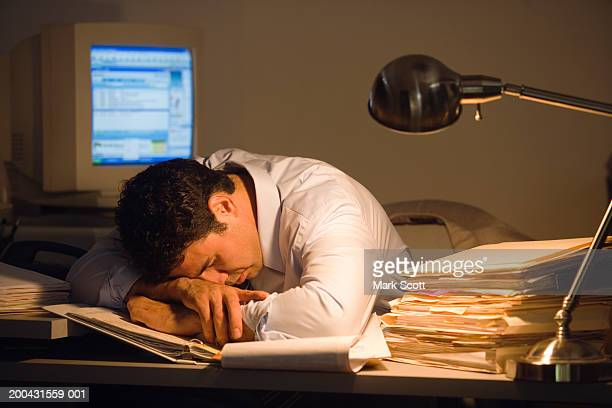 Young businessman sleeping on paperwork in office