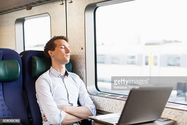 Young businessman sleeping on train