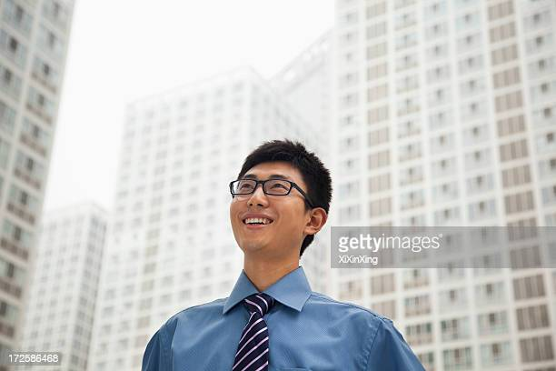 Young businessman smiling and looking at the sky