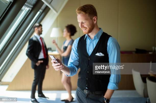 Jeune entrepreneur souriant et envoyer des SMS message