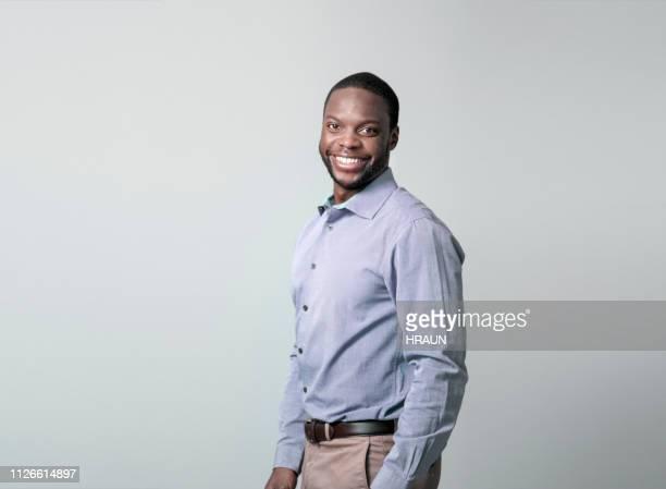 jovem empresário sorrindo sobre fundo cinza - roupa formal - fotografias e filmes do acervo
