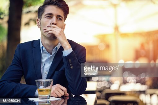 Young Businessman Smoking Cigarette And Sitting On The Par