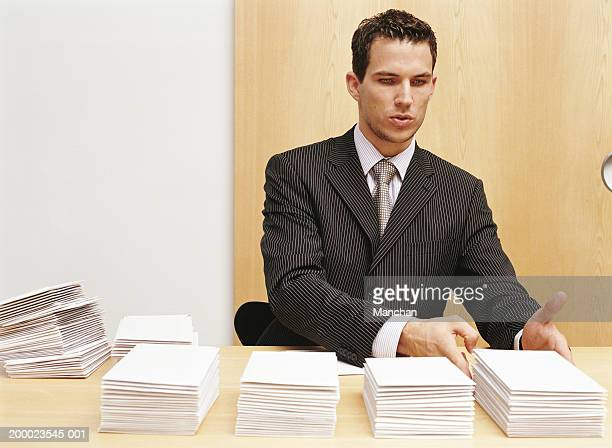 Young businessman stacking envelopes on desk