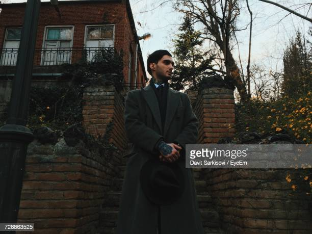 Young Businessman Standing Against Building