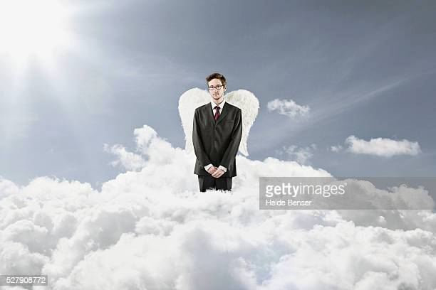 Young businessman standing around clouds with angel wings