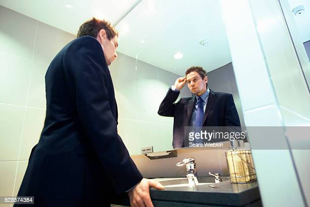 Young Businessman Standing at Mirror in Public Restroom