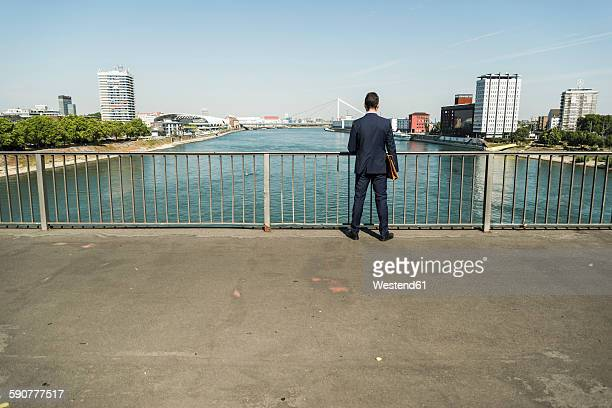 Young businessman standing at railing looking at river