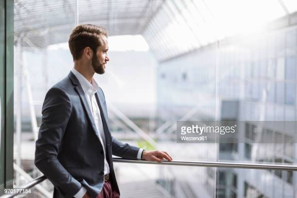 Young businessman standing at railing