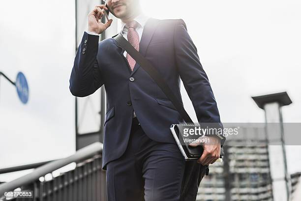 Young businessman standing at railing, using smart phone