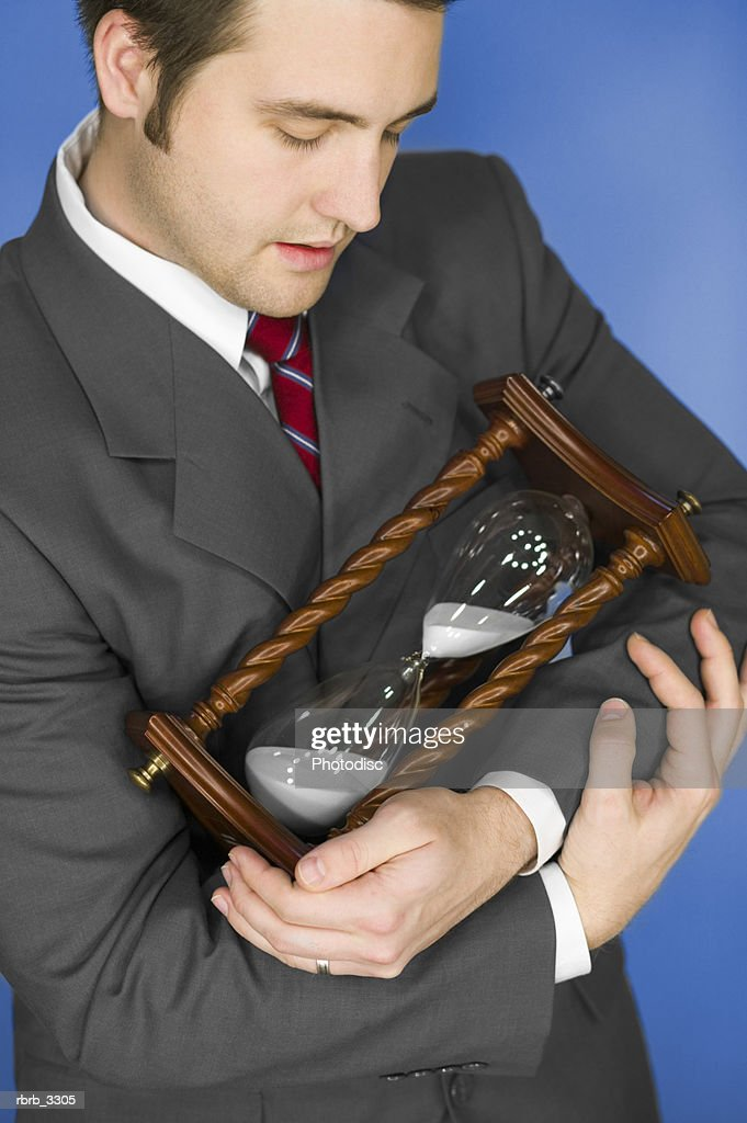 Young businessman standing holding an hourglass : Stockfoto