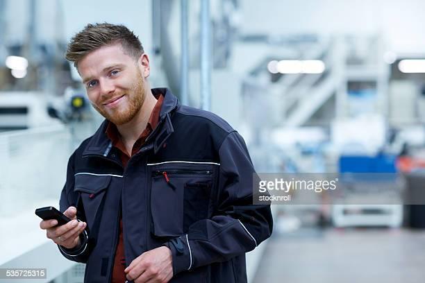 Junger Geschäftsmann, stehen in Fabrik mit einem Handy