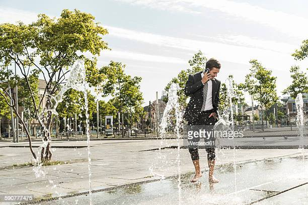 Young businessman standing in fountain, talking on the phone