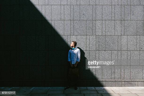 Young businessman standing in front of a grey wall looking up
