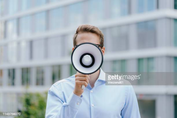 young businessman standing in front of modern office building, using megaphone - megaphone stock pictures, royalty-free photos & images