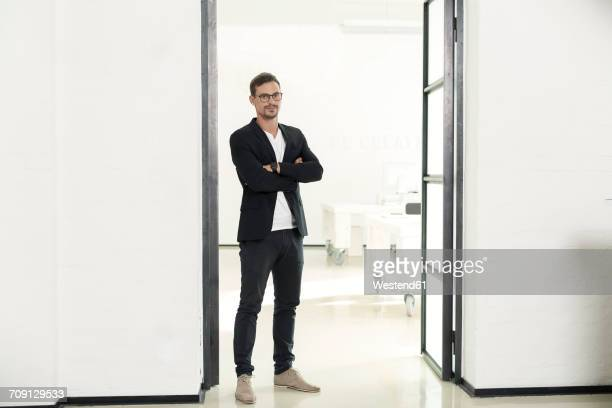 young businessman standing in his office with arms crossed - ganzkörperansicht stock-fotos und bilder