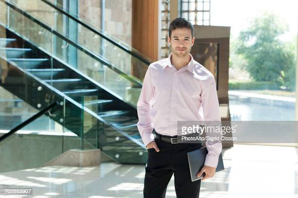 Young businessman standing in hotel lobby