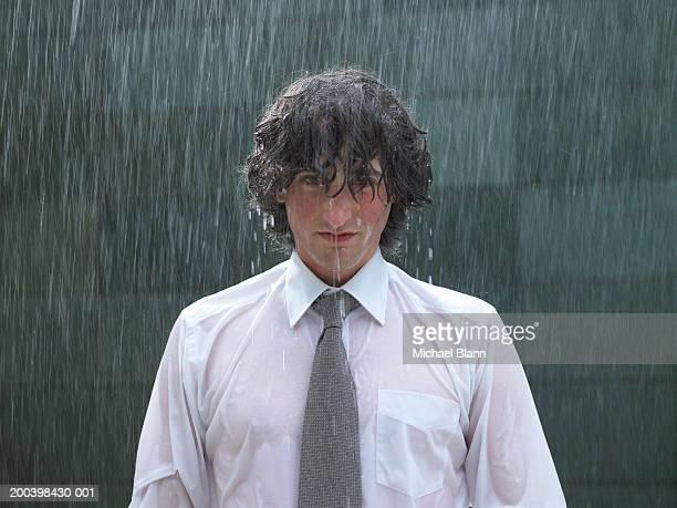 young businessman standing in rain, portrait, close-up - nat stockfoto's en -beelden