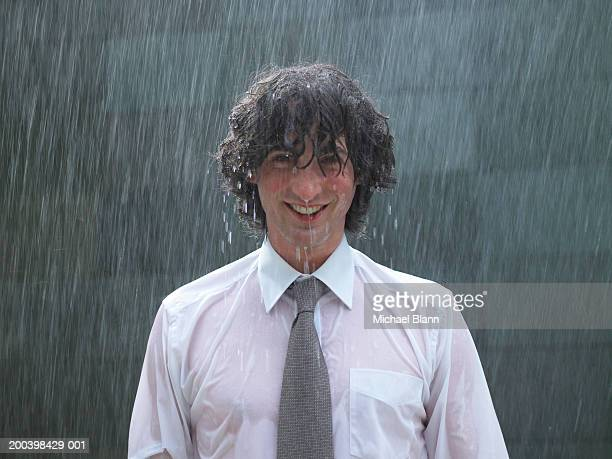 young businessman standing in rain, smiling, portrait, close-up - bagnato foto e immagini stock