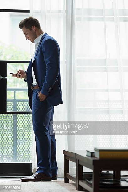 Young businessman standing inside and text messaging, New York City, New York State, USA