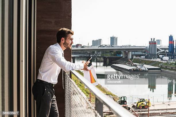 young businessman standing on balcony looking at view - mannheim stock-fotos und bilder