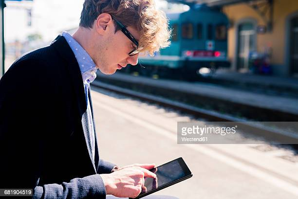 Young businessman standing on platform using mini tablet