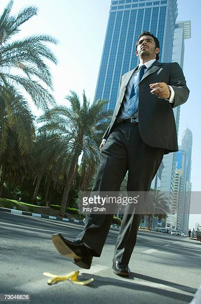 Young businessman stepping on banana peel