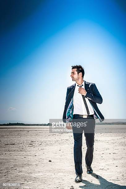 young businessman striding through desert landscape alone - colarinho aberto - fotografias e filmes do acervo